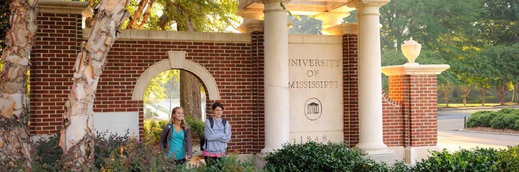 Students walking in front of a brick archway on campus.