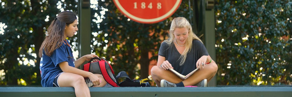 A student sits on the stage in the Grove reading.